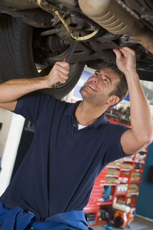 Mechanic working under car smiling photo