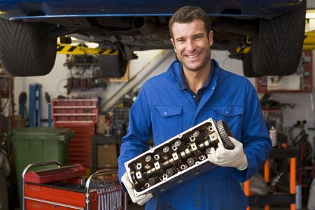 motor mechanic: Mechanic holding car part smiling Stock Photo
