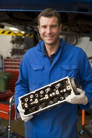 Mechanic holding car part smiling photo