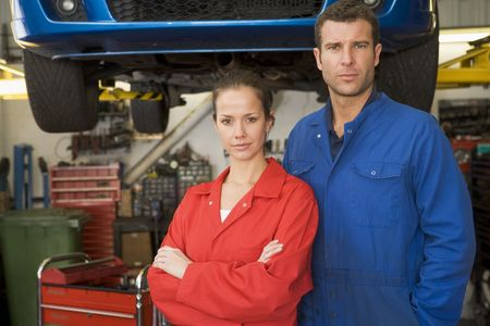 motor mechanic: Two mechanics standing in garage