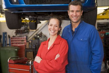 Two mechanics standing in garage smiling photo