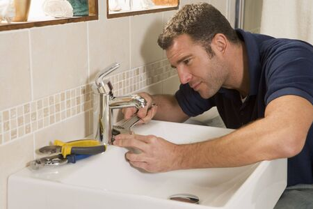 Plumber working on sink photo