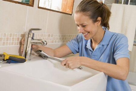 Plumber working on sink smiling photo