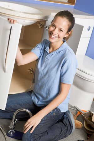 Plumber working on sink smiling photo