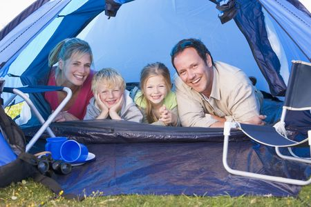 campsite: Family camping in tent smiling