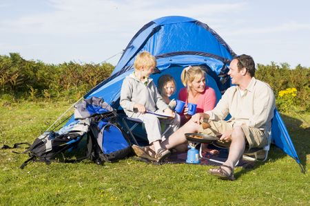 Family camping with tent and cooking photo