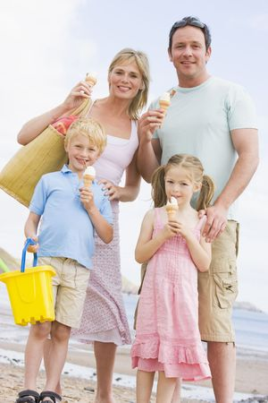 ice cream stand: Family standing at beach with ice cream smiling