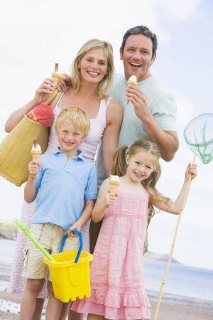 una familia comiendo: Familia de pie en la playa con helado sonriente