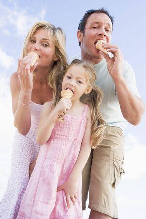 familia comiendo: Familia de pie al aire libre con helado