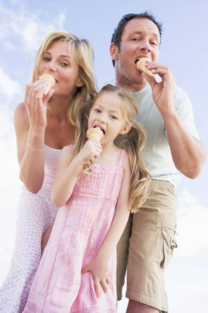 outdoor eating: Family standing outdoors with ice cream Stock Photo