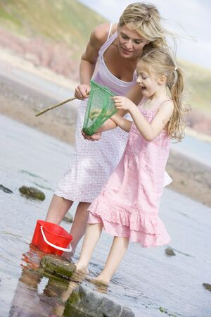 Mother and daughter at beach fishing and smiling Stock Photo - 3603000
