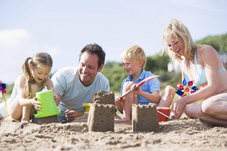 Family on beach making sand castles smiling Stock Photo - 3601594