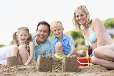 Family on beach making sand castles smiling photo