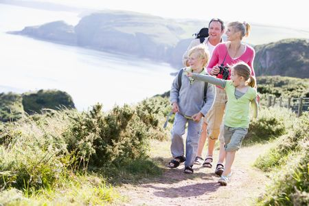 ruck sack: Family walking on cliffside path pointing and smiling Stock Photo