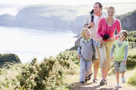Family walking on cliffside path holding hands and smiling photo