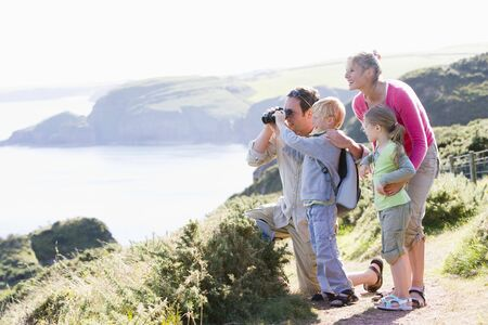 rambler: Family on cliffside path using binoculars and smiling