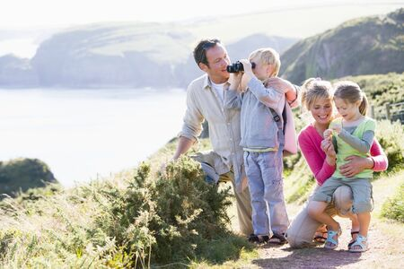 Family on cliffside path using binoculars and smiling photo