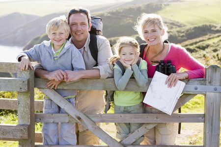 ruck sack: Family on cliffside path leaning on fence and smiling