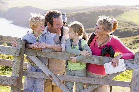 rambling: Family on cliffside path leaning on fence and smiling