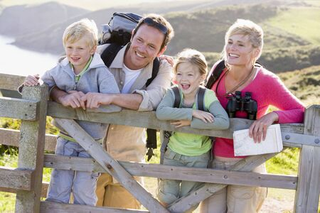 Family on cliffside path leaning on fence and smiling photo