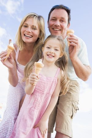 Family standing outdoors with ice cream smiling photo