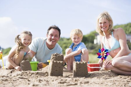 Family on beach making sand castles smiling Stock Photo - 3601505