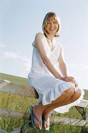 Woman sitting on fence outdoors smiling photo