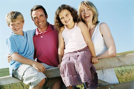 Family on fence outdoors smiling Stock Photo - 3603155