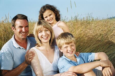 Family sitting outdoors smiling photo