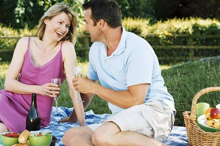 Couple sitting outdoors with picnic smiling photo