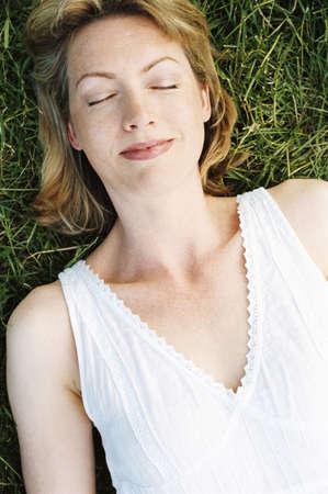 Woman lying outdoors sleeping photo