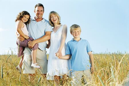 countryside loving: Family standing outdoors holding hands smiling