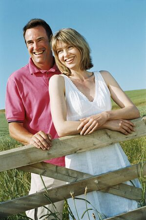 Couple standing outdoors by fence smiling photo