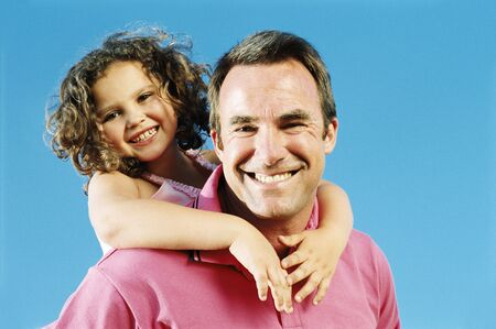 Father giving daughter piggyback ride outdoors smiling photo