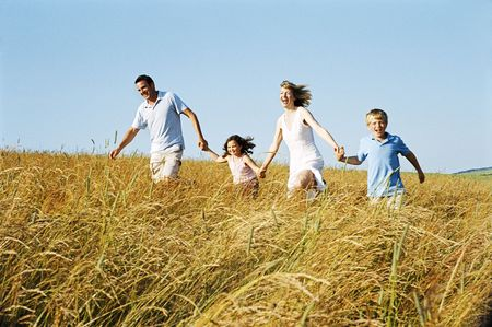 Family running outdoors holding hands smiling photo