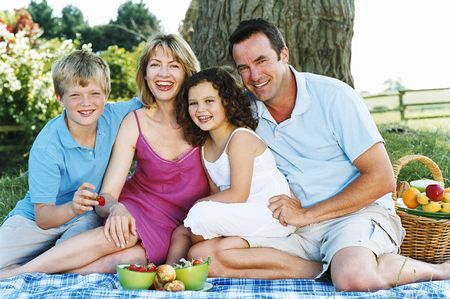 Family sitting outdoors with picnic smiling photo