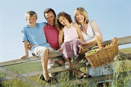Family outdoors by fence with picnic basket smiling photo