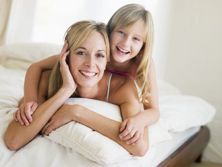 Woman and young girl lying in bed smiling photo