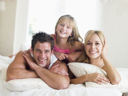 Family lying in bed smiling photo