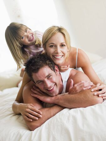 Family in bed playing and smiling photo