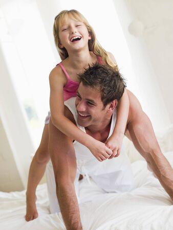 pere et fille: L'homme et la jeune fille dans le lit de jouer et sourire