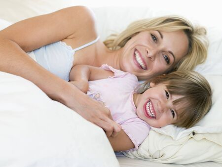 Woman and young girl in bed smiling photo