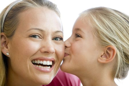 Young girl kissing smiling woman photo