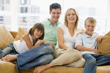 Family sitting in living room smiling Stock Photo - 3602962