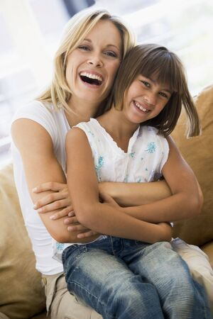 Woman and young girl sitting in living room smiling photo