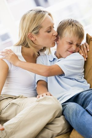 Woman kissing disgusted young boy in living room Stock Photo - 28232235