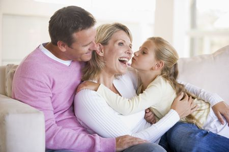father daughter: Family in living room with young girl kissing woman