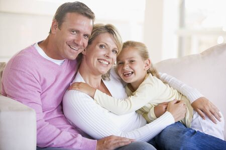 Family sitting in living room smiling Stock Photo - 3601432