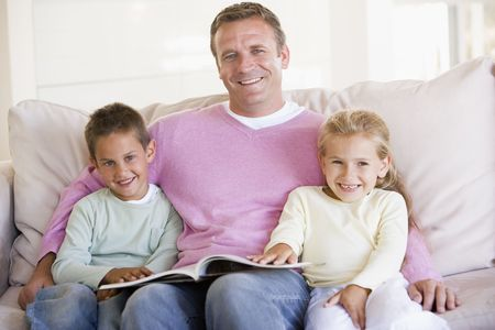 Man and two children sitting in living room reading book and smiling Stock Photo - 3602736