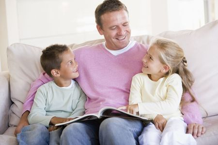 stories: Man and two children sitting in living room reading book and smiling
